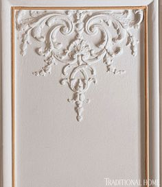 "Elegant Molding Details Ornate plaster molding adorns the living room wall panels, which are painted ""China White"" from Benjamin Moore."