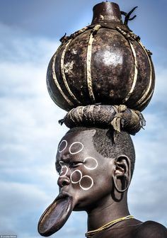Traditionally the Suri women take care of the household and child rearing and tend to fields of sorghum, maize, beans, tobacco. The women's pot was used to carry sorghum beer a much loved beverage amongst both male and females