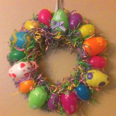 Easter wreath made by using plastic eggs from dollar tree, Easter grass, foam board, ribbon, and hot glue....not too shabby!