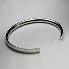 Contemporary solid inverted D-section bangle which is flat on the outside and curved on the inside. This is a great slim close-fitting cuff and is a very understated, stylish design that is perfect for men and women. Personalise this bangle with a special message engraved around the inside or outside of the bangle. How thoughtful! Available in a variety of precious metals. Please note that the letter (style 3) engraved bangle is an example only. If you want to add engraving please do so…