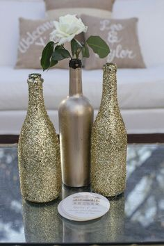 DIY Sparkly Gold Wine Bottles- These are pretty! Perfect for wedding decor if the middle one was a matte black