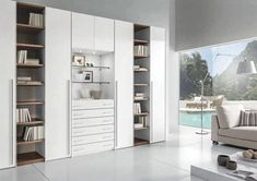 A Symmetrical Tall Storage Unit with 4 Enclosed Shutters with Long Handles, 2 Open Display Column of Shelves & a Center part consist of multiple Drawers & Glass Shelves above with an Under Unit ✨ Light - GharPedia Modern Bookshelf, Bookshelves, Bookshelf Ideas, Solid Wood Furniture, Furniture Design, Modular Wardrobes, Home Furniture Online, Bedroom Wardrobe, Minimalist Bedroom