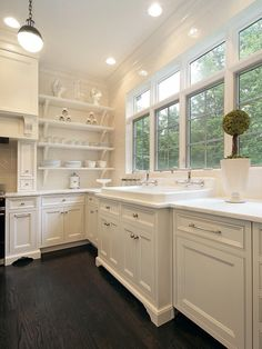Ooooh, my kids would make this so dirty. But it's beautiful. Love the contrast of the dark floor and the white. Also love the sink and windows.