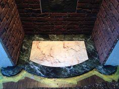 Twee soorten marmer imitaties op de bodemplaat van een schouw.