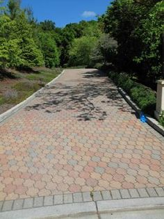 Pacific Interlock's Roma pavers in B4 (red/tan/charcoal) framed with Holland in Charcoal make this driveway so welcoming.
