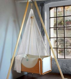 According to some, a hanging crib makes the transition from womb to world a little easier for your baby. Suspended cradlesImage viaThe hanging cradle provides a Baby Bassinet, Baby Cribs, Baby Bedroom, Kids Bedroom, Hanging Cradle, Hanging Crib, Mini Greenhouse, Baby Swings, Baby Hammock