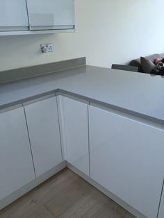 Grey granite worktop, white handless high gloss kitchen (howdens), wooden floor