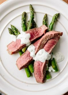 "Here's a super quick dinner for your springtime arsenal — meaty sirloin tip steaks (sometimes called ""charcoal steaks"" or ""knuckle steaks,"" depending on where you live) cook oh-so-quickly on a wire rack under the broiler, while the asparagus below soaks up all of the flavorful juices from the meat. An easy blender sauce with punchy chives and feta makes a great accompaniment."