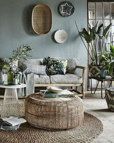 Green living room with all natural furniture and accessories. Woven coffee table and wall decor. Wooden chair with neutral cushions and room filled with plants.