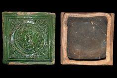 Fragment einer Blattkachel mit ringhaltendem Löwenkopf in lorbeerblattbesetztem, rundem Medaillon, grün glasiert, 17. Jh., H. 17,5 cm, Br. 17,7 cm, Ettlingen, Albgaumuseum, urspr. Ettlingen, Färbergasse