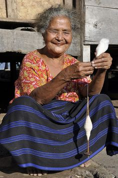 Spinning woman from Indonesia ... Not sure what she's spinning...guessing cotton.