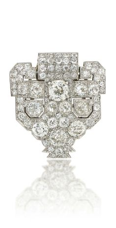 AN ART DECO DIAMOND CLIP BROOCH, BY CARTIER Of shield form, entirely pavé-set with old brilliant-cut diamonds, with pierced geometric detailing, circa 1930, 3.2cm long Signed Cartier, no.3217939