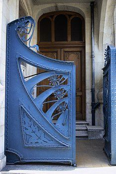 An Art Nouveau style iron gate decorated with plant forms, visible rivets, and characteristic sinuous curves, stands open at 22 Rue de la Commanderie in Nancy. Architects Georges Biet and Eugene Vallin designed the building and ironwork.