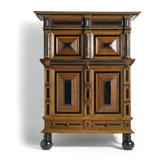 A DUTCH OAK, EBONISED AND ROSEWOOD CUPBOARD, BAROQUE, SECOND HALF 17TH CENTURY the upper section with two panelled doors flanked and divided by pilasters, above a drawer decorated with lion's masks, lower section with two panelled doors and one drawer, on ball feet   height 235cm., width 183cm., depth 75cm.