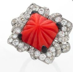 An Art Deco platinum and enamel ring with diamonds and coral. The ring centers on a square carved coral pyramid that is set with black enamel prongs. It is framed with old European cut diamonds.  Macklowe Gallery.