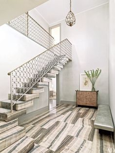 Architect David Mann enhanced the double-height entrance hall of this New York City apartment with a pendant light and an antiqued-brass-and-silver railing,