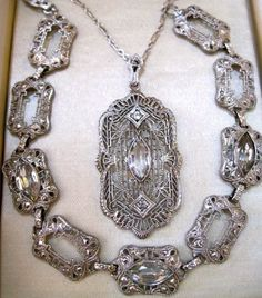 Gorgeous set art deco era sterling silver necklace & bracelet. Bracelet is filigree rectangle sterling boxes with marquis shaped faceted crystals. Pendant is sterling filigree with a center marquis crystal & one little crystal above & below the center. Original figure 8/paper clip sterling chain.