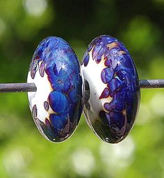 """A pair of disc-shaped beads in a base of off-white. The beads were rolled in striking frit, which struck to beautiful deep blues and purples.  The dimensions are: 8.8mm (.34"""") hole-to-hole, 19mm (.75"""") wide, with a 2.6mm hole"""
