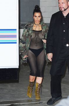 Kim Kardashian left little to the imagination in this net dress--which she paired with lace up booties, a tie-choker, and a camo jacket.