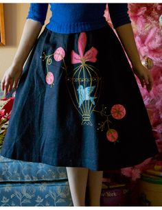 Doesn't get much more 50s than this! A black felt skirt, with an amazing bluebird applique! The bird (with a rhinestone eye) has it's wings spread in a golden cage, topped with a pink bow. Pink and gold circles branch out from the cage, dotted with rhinestones. Skirt has an elastic waist, and is therefore slightly gathered.