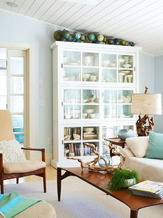 A simple white bookcase with glass doors is and ideal spot to showcase nautical collections in a beach home. (via @Better Homes and Gardens www.bhg.com)