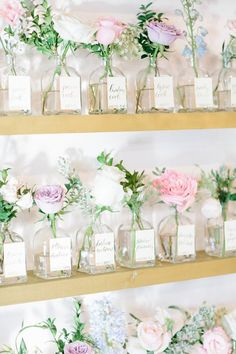 Glass bottles with flowers as escort cards.