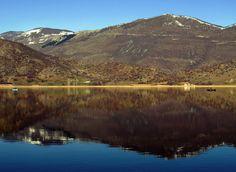 Lake Zazari with Mount Vitsi n de road close to de top leads to Nymfaio, one of de mountainous Greek villages, hidden behind de peak. De building in de background is de guesthouse. Limnohori, Florina, Macedonia_ Greece