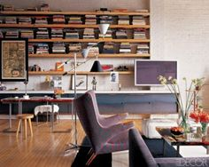 In this Manhattan loft designed by Joe D'Urso, long, linear shelves complement the apartment's modern look. Stacking the books horizontally in small piles gives the whole ensemble a sculptural impression while also making the spines easier to read. The spacing between the stacks can also be changed easily, allowing the insertion of objets d'art.  Photographer: William Abranowicz