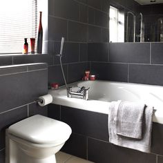 Charcoal Tiled Bathroom With A White Bath And Toilet