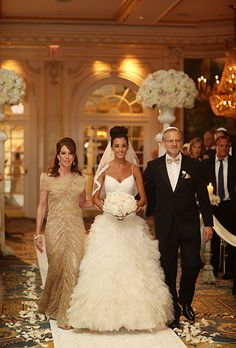 """Brides.com: A Glamorous Summer Wedding in New York City. Mallorie's mother and father escorted her down a white aisle dotted with rose petals. """"I wanted a big entrance,"""" the bride explains, so two white-washed Roman pedestals topped with floral arrangements flanked the end of the aisle. For more wedding inspiration, check out pinterest.com/barefootbridalx"""