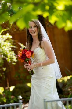 Fall bride with gorgeous bouquet in reds, tangerines and coral hues.  Flowers: Visual Impact Design  Photo: Sharpe Weddings  Venue: Newcastle Wedding Gardens