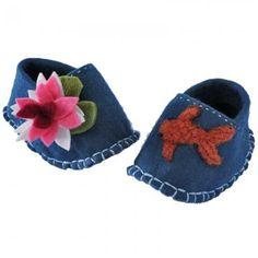des chaussons pour bébé en feutre turquoise avec un nénuphar en feutre rose et vert sur le pied gauche et un poisson orange en laine cardée sur le pied droit.