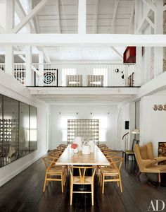 In the same home, the double-height formal dining area, also in a former barn, is furnished with chairs designed by Hans J. Wegner for Carl Hansen & Son and a custom-made table by India Mahdavi.