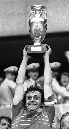 French team captain and midfielder Michel Platini is all smiles as he holds aloft the winner's cup after France defeated Spain 2-0 in the final of the UEFA Euro 1984, at the Parc des Princes in Paris, earning France their first-ever European title, 27 June 1984, Paris, France. Michel Platini, All Smiles, No One Loves Me, Fifa, First Love, Soccer, Football, Paris France, Classic