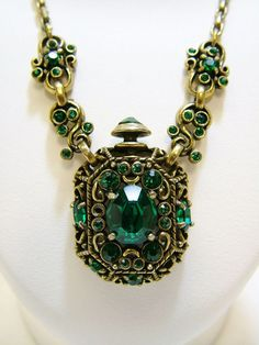"""*1951  Hollycraft perfume bottle pendant necklace.  The pendant  has a beautiful design with emerald green rhinestones set into it.  There are two links on each side of the bottle that also have rhinestones, the clasp has two rhinestones, and the """"topper"""" to the bottle is crowned with a rhinestone as well.  The pendant measures 3,5cm"""