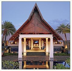 Balinese resort w/ white-tapered columns and thatched roof