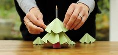 This tutorial shows you how to take several circles of recycled paper (from sixteen centimenters to four centimeters in diameter). Fold each of them in half several times, then cut a hole in the tip. Then just stack and decorate!