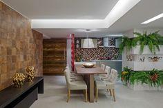 No Apartamento do Casal Moderno, projetado por Luciana Herenio, Cecília Malcher e Cristina Braz, a parede acima da bancada da cozinha tem acabamento com estampa geométrica multicolorida. Ao lado da mesa de jantar, outra parede possui recortes que abrigam samambaias e bromélias, além de objetos de decoração.