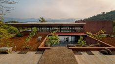 Indian architecture office Red Brick Studio has completed a house in the Western Ghats mountain range featuring a curved roof that is lifted above pigmented-plaster walls. The Cove House was designed as a retreat for a client who wanted to escape his busy life in the city and enjoy weekends in the mountainous region near Pune. Brick Studio, Studio Floor Plans, Coving, Clerestory Windows, Architecture Office, Indian Architecture, Plaster Walls, Red Bricks, Stone Flooring