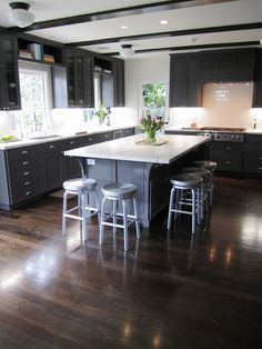 Kitchen with dark grey cabinets and drawers, school house lighting and dark stained wood beams, marble counter tops, wood floor, and metal barstools around a large island with a marble top