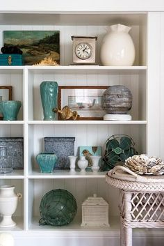 For continuity, or to showcase a collection, choose a main color (or two) to carry through your shelves, like the turquoise and white pieces shown below that are a common color theme.