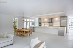 Set against a polishedwhite backdrop, thewooddining table and chairs positivelypopat thisconcrete and granite home in Florida.    This originally appeared in Passive Materials Cool this Bright White Tropical Home.