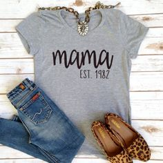 Custom graphic tees with a name and est. date! Makes a perfect gift for Mother's Day! Customize your Est. Date Tee: Enter a name up to 15 characters Enter an est. year. Please enter the name as you would like it to appear and proofread both the name and date before submitting your order. Your custom design is direct to fabric print that results in a super soft design that won't crack or fade! Shirt Info & Sizing: LADIES FIT : Slightly contoured, shorter sleeve & body length, f...
