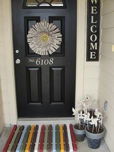 cute entry- door, wreath, welcome sign, pinwheels, & wood plank rug. love it!