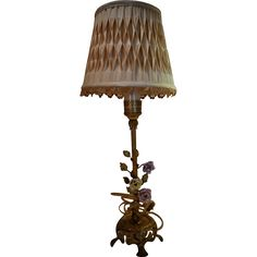 This elegant 1930s brass boudoir lamp is in the French style, with porcelain flowers and brass leaves and a footed base. It retains the original silk