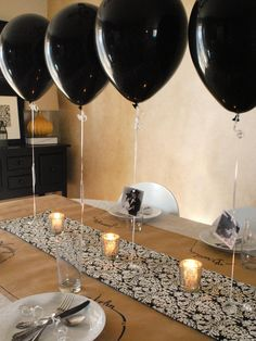 "To create this party-ready centerpiece and table, Wendy Hyde of The Shabby Nest first layered kraft paper over a neutral tablecloth and topped it with a black-and-white patterned table runner. ""Balloons were tied to chandelier crystals to weigh them down and keep their place on the table,"" she says. ""Pretty mercury-glass votives were placed between the balloons to add ambient lighting."" For a personalized touch, each balloon was embellished with photographs, in this case, pictures of the…"
