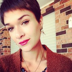 a true pixie cut with a cateye and pink lips