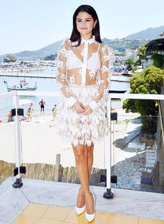 Selena Gomez @ Ischia Film Festival in Blumarine Embroidered Rose and Tulle Blouse and Feather-Embellished Tulle Skirt; Cosabella Dolce Soft Bra in White; Casadei Stiletto Pumps.