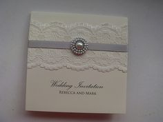 Lace wedding invitation with a pearl and satin ribbon. Shown in Silver