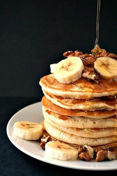A stack of fluffy American pancakes topped with sliced bananas and walnuts and honey drizzling all over them